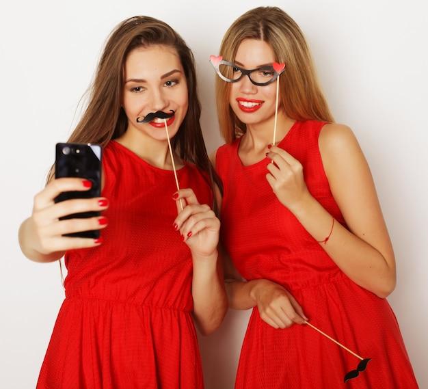 赤いドレスを着て自分撮りをしている2人の若い女性