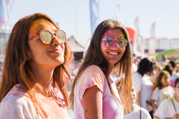 Two young women wearing sunglasses with holi powder on face