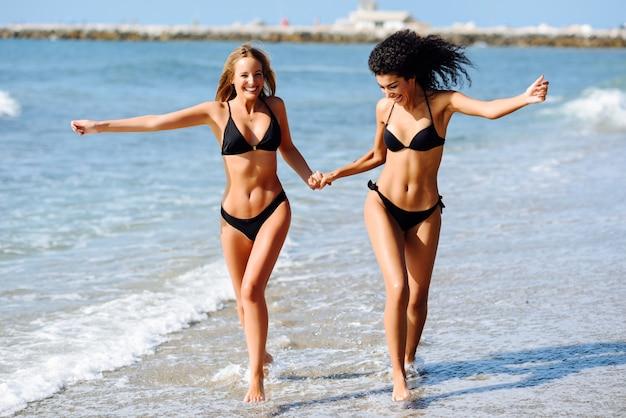 열 대 해변에서 수영복에 아름 다운 시체와 함께 두 젊은 여성.