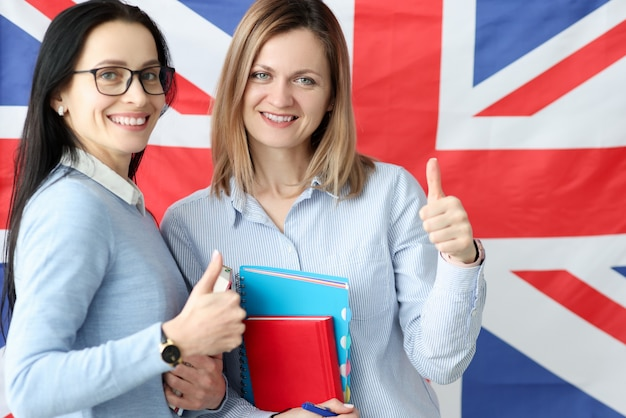 Two young women with books in hands standing against background of british flag. learning of