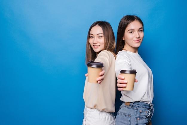 파란색 벽에 고립 갈 커피 컵과 두 젊은 여성