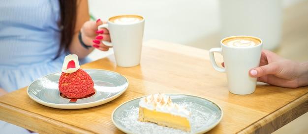 Две молодые женщины с чашками кофе и кусками торта, сидя за столом в кафе на открытом воздухе