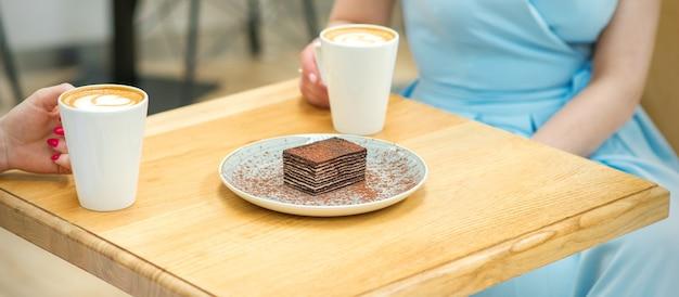 커피 컵과 야외 카페에서 테이블에 앉아 케이크 조각 두 젊은 여성