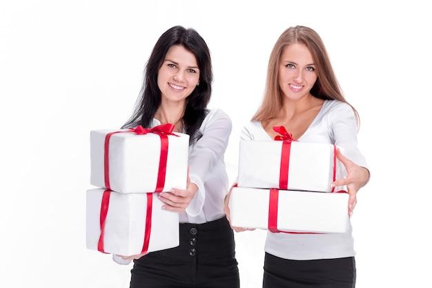 Две молодые женщины с подарочными коробками. изолированные на белом фоне