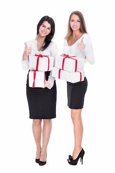 엄지손가락을 보여주는 선물 상자와 두 젊은 여성. 흰색 배경에 고립