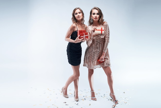 Two young women with red presents in hands isolated on white