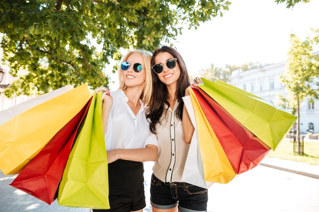 Two young women with shopping bags on the city street having fun