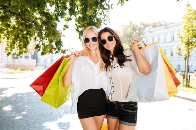 Две молодые женщины с хозяйственными сумками на городской улице веселятся