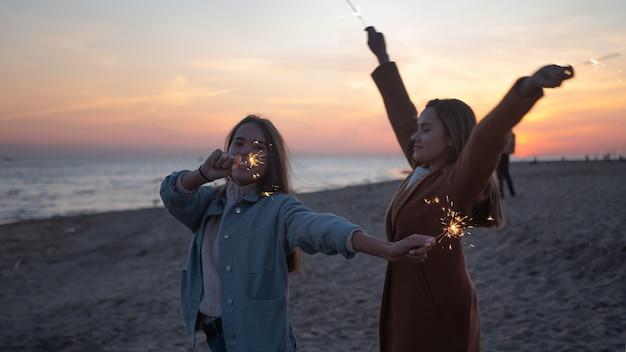 Две молодые женщины с бенгальскими огнями на открытом воздухе. друзья веселятся на пляже, счастье и чувство свободы, закат в сумерках