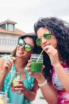 屋外でストローと健康的な有機飲料を飲むサングラスをかけた2人の若い女性