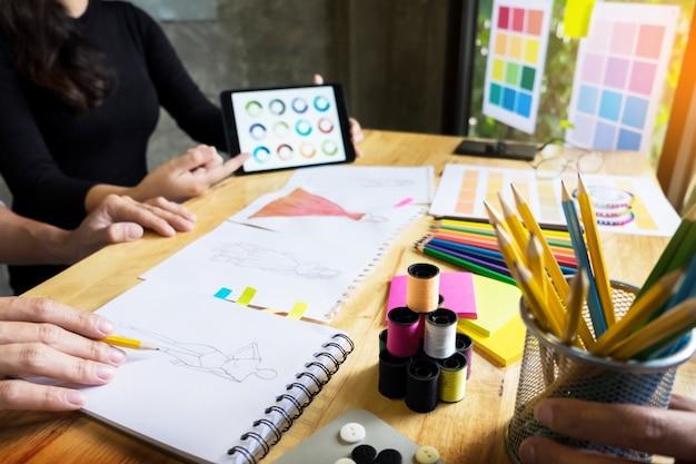 2人の若い女性がファッションデザイナーとして働き、スケッチを描き、カスタムテーラーでファブリックのアドバイスを受け取ります