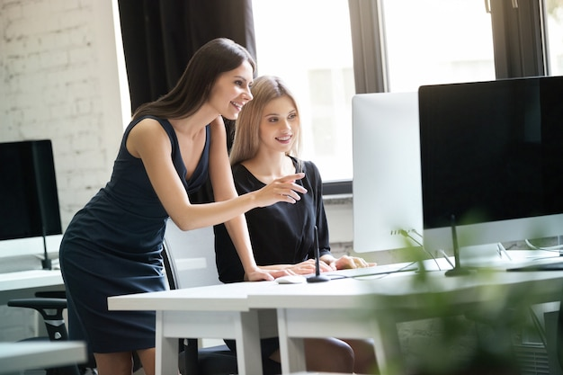 Two young women working together with computer