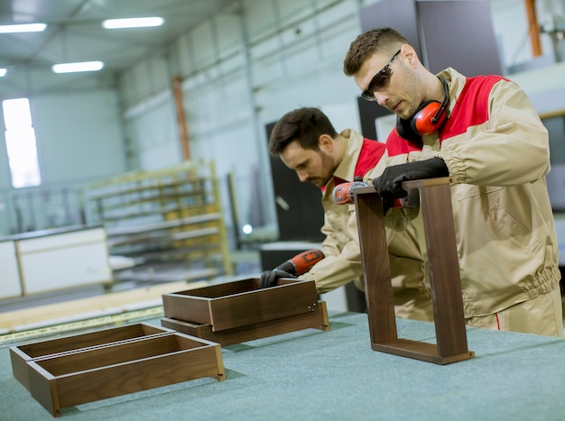 Two young workers assembling furniture in the factory