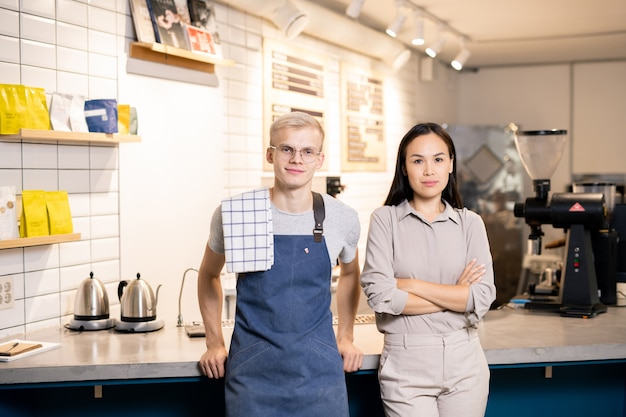 Two young workers of contemporary cafe or restaurant standing by workplace in front of camera and looking at you