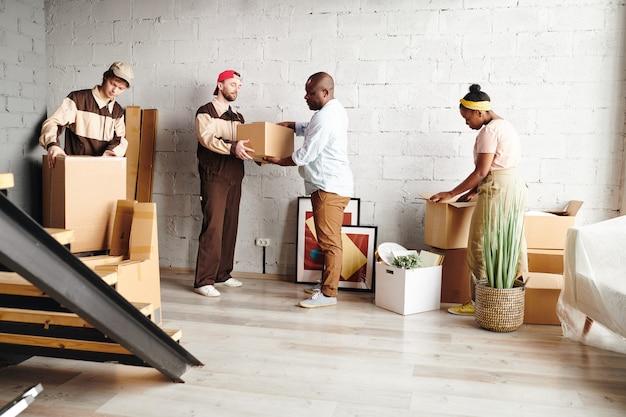 제복을 입은 두 명의 젊은 노동자가 결혼한 아프리카 부부가 제거하는 동안 포장된 상자를 새 아파트나 집으로 배달하는 것을 도왔습니다.