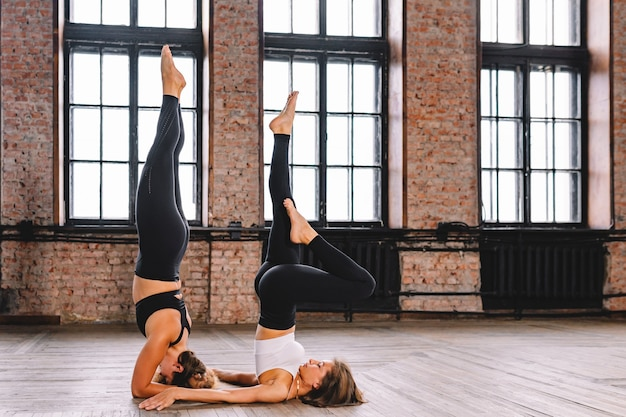 Две молодые девушки выполняют комплекс асан йоги на растяжку в классе лофт. поза ширшасаны.