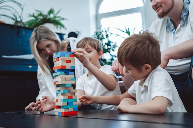 Two youth boys construct a tower from bricks competing each other and with their parents at home.