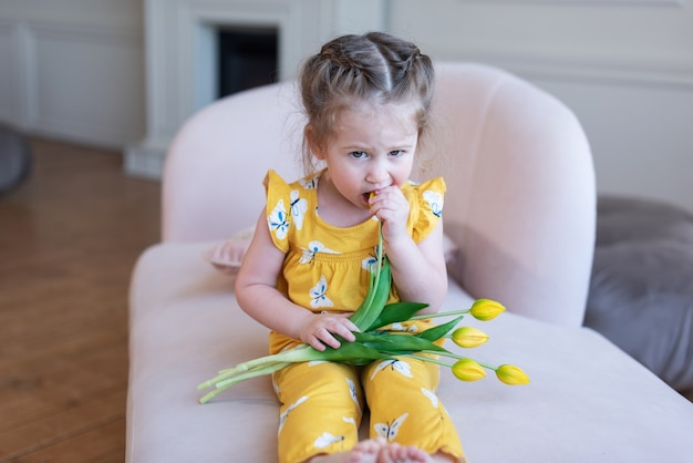 A twoyearold cute beautiful girl in a yellow suit sits on the sofa and holds yellow tulips in her