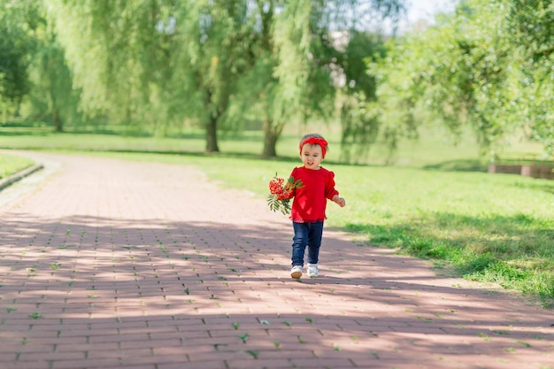 A twoyearold girl runs around the park with a bouquet with a serious expression on her face