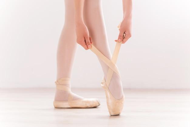 그녀의 슬리퍼를 묶는다. 나무 바닥에 서 있는 동안 슬리퍼를 신고 있는 발레리나의 클로즈업