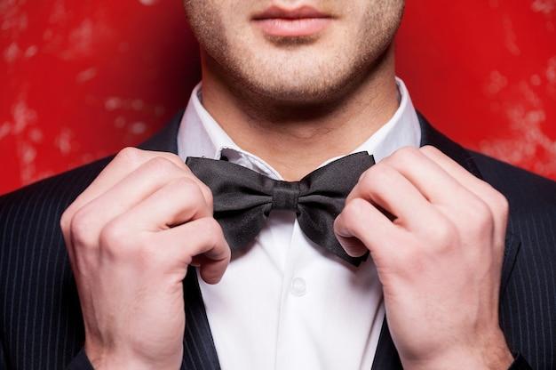 彼の蝶ネクタイを結ぶ。赤い背景に立っている間彼の蝶ネクタイを調整する正装でハンサムな若い男のトリミングされた画像