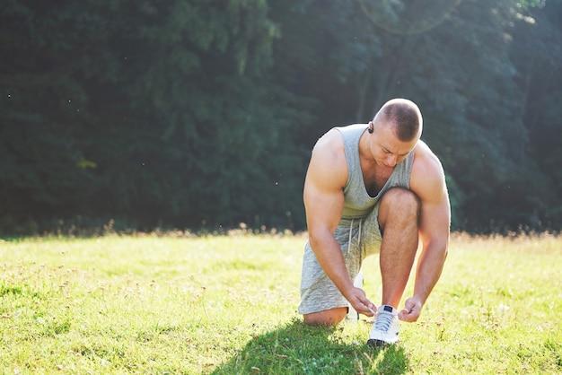 スポーツシューズを結ぶ。屋外での運動とフィットネスのトレーニングの準備をしている若いスポーツマン。