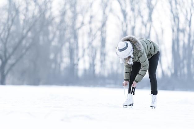 얼어 붙은 호수에서 겨울 스케이트 끈 묶기, 아이스 스케이트