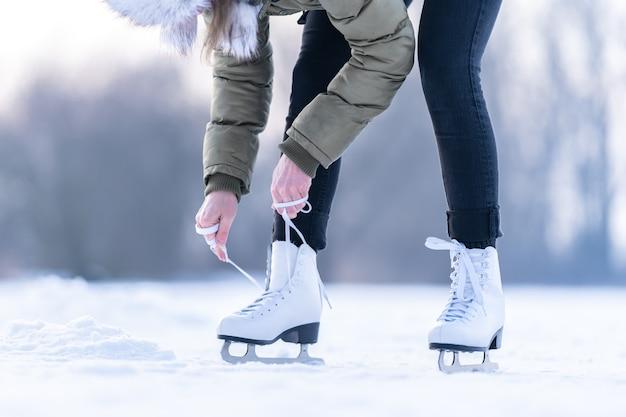 凍った湖で冬のスケート靴のひもを結ぶ、アイススケート