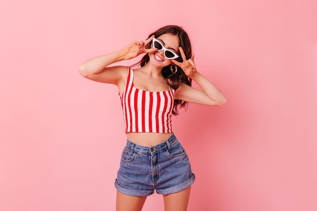 Tylish темноволосая женщина в летних шортах и топе улыбается и показывает знак мира на розовой стене