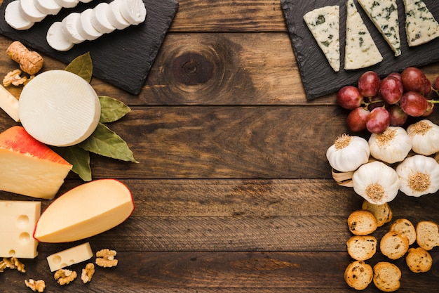 Types of cheese and ingredient on old wooden background