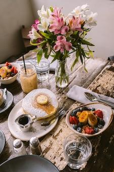 花瓶の前のテーブルに置かれる食べ物、クッキー、飲み物の種類