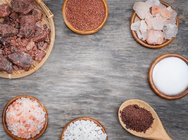 塩の背景の種類。木製のテーブルの上のいくつかの種類の塩