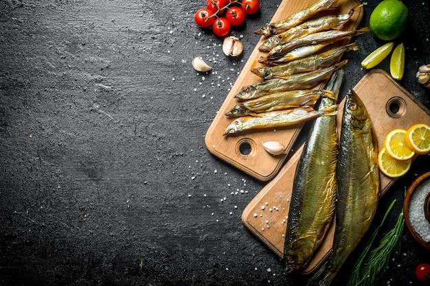 黒の素朴なテーブルにライム、レモン、トマト、ハーブのスライスを添えた魚の燻製の種類。