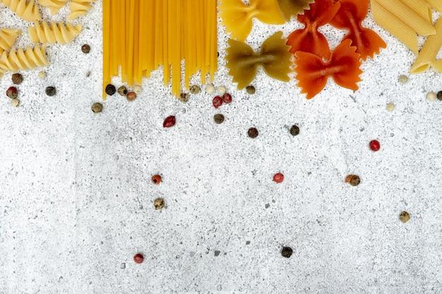 未調理パスタの種類。パスタペンネ、フジッリ、ファルファッレ、スパゲッティ、カラフルなエンドウ豆は、明るいコンクリートの背景で乾きます。上からの撮影。フラット横たわっていた、トップビュー、コピースペース