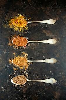 ダークテーブルのスプーンでさまざまなスパイスの種類。