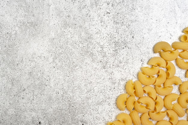 Types of uncooked pasta on concrete background