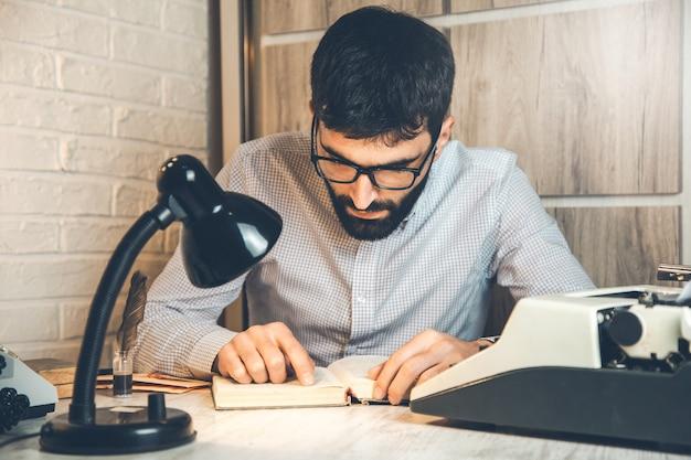 Пишущая машинка и человек, читающий книгу на столе