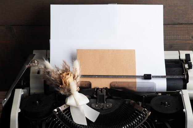 タイプライターはクローズアップし、封筒で花を乾かします。バレンタインのコンセプト、ヴィンテージトーンとクラフト紙