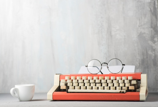 A typewriter and an espresso cup