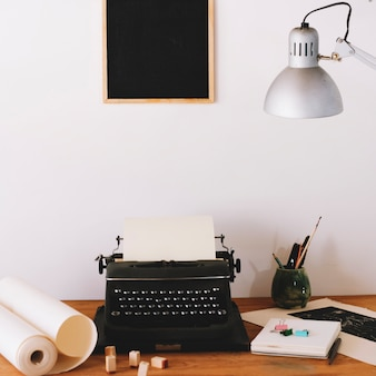Typewriter and office supplies on table