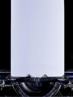 クリアホワイトの長いページと黒の背景のタイプライター。垂直方向の向き
