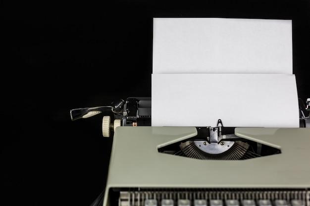 빈 공간을 가진 백서와 검은 벽에 테이블에 타자기. 작가 또는 작가의 직장. 새로운 생활 개념.