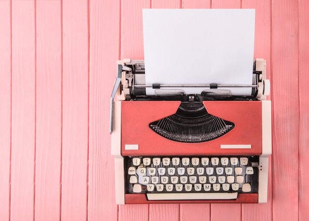 A typewriter on a pink table (top view)