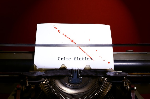Typewriter spelling crime fiction on paper with blood splashes.