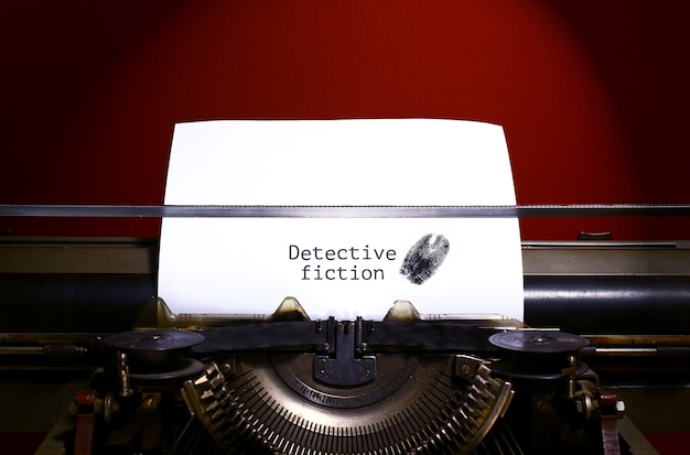 Typewriter spelling detective fiction on paper with finger print.