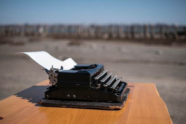 Typewriter on the table in the open air, estuary on the background