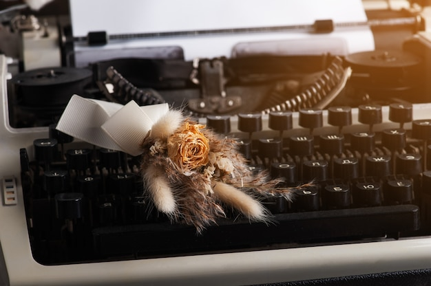 Typewriter with russian letters close up and dry flowers