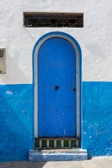 アシラーの典型的なアラビア建築。通り、扉、窓、お店。モロッコ