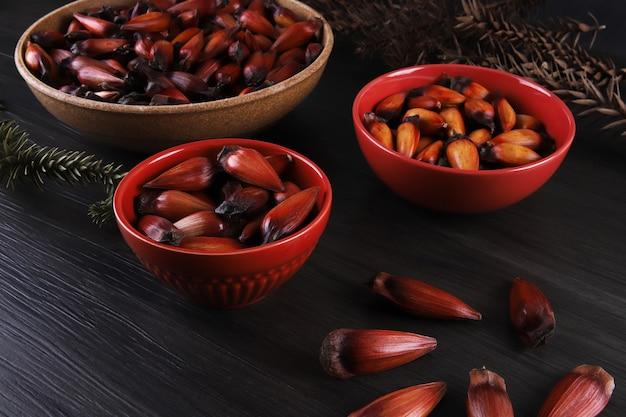 겨울에 브라질 요리의 조미료로 사용되는 전형적인 아라우카리아 씨앗. 회색 나무 배경에 갈색과 빨간색 나무 그릇에 브라질 피니언 너트.