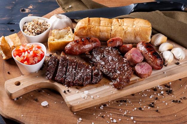 마늘 빵, picanha, 소시지, vinaigrette 및 farofa와 함께 전형적인 브라질 바베큐